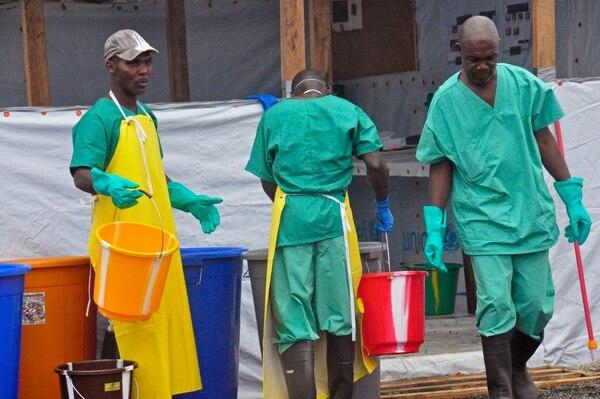Trabajadores de salud, con equipo de protección, laboran en un centro de atención contra el ébola en Monrovia, Liberia.