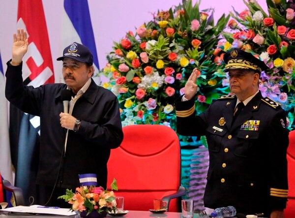 El presidente de Nicaragua, Daniel Ortega estrecha la mano del nuevo comisionado Francisco Díaz (padre del hijo de Ortega) durante el 39º aniversario de la Policía Nacional en Managua. Foto: AFP