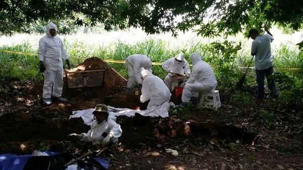 Expertos forenses trabajan en el sitio donde las autoridades mexicanas localizaron una fosa con al menos 11 cuerpos.