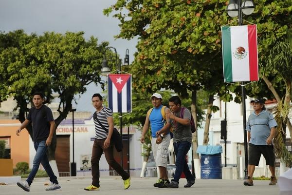 Habitantes caminan frente a banderas de Cuba y México en la ciudad mexicana de Mérida, donde se reunirán este viernes el presidente de México, Enrique Peña Nieto, y su homólogo de Cuba, Raúl Castro.