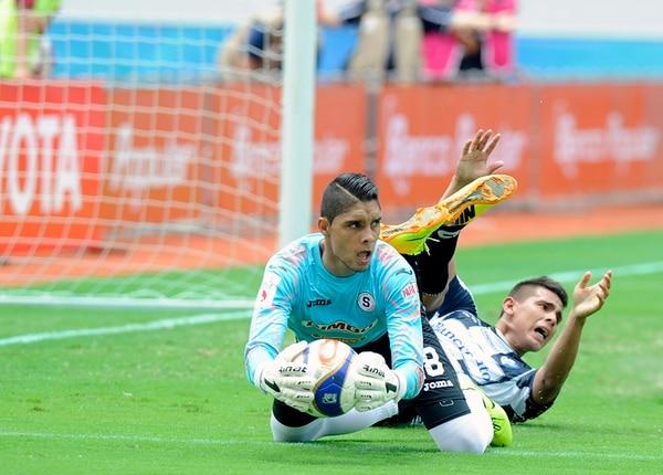 El portero morado Kevin Briceño le gana la posesión del balón al delantero del Club Sport Cartaginés, Andrés Lezcano.   GRACIELA SOLÍS
