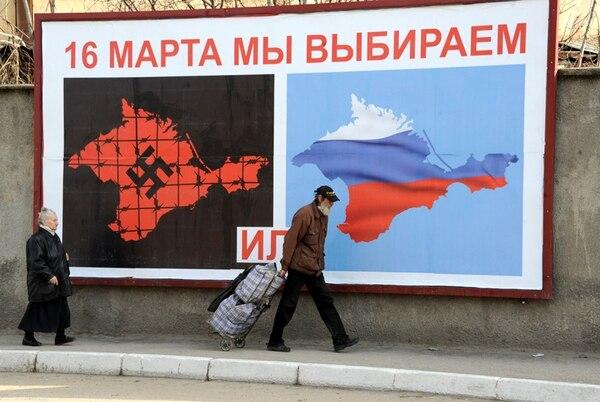 Transeúntes pasan frente a un afiche en Sebastopol que hace alusión al referendo del domingo. A la izquierda, se representa a una Crimea bajo dominio nazi; la otra imagen muestra el anhelo de los prorrusos. | AFP
