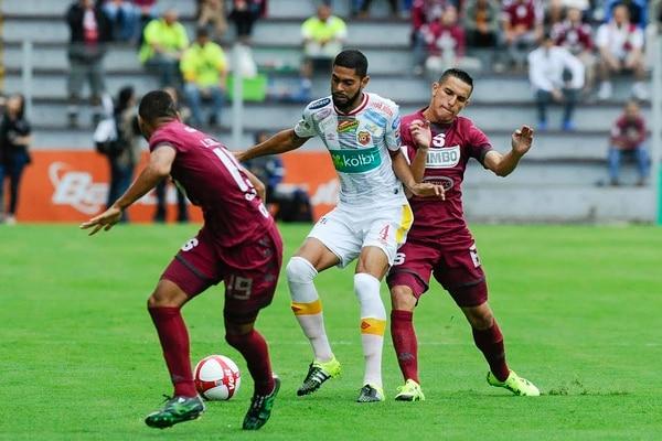 El defensor de Herediano Allan Miranda intercepta el balón que iba dirigido al saprissiat David Guzmán.