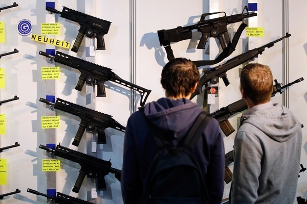 (FILES) In this file photo taken on March 29, 2019, visitors look at semi-automatic shotguns displayed on a wall during the 45th edition of the Arms Trade Fair, in Lucerne. - The Swiss will vote on May 19, 2019, on whether to bring the country's gun laws in line with EU legislation, with the government warning a 'no' could threaten relations with the bloc. A demand from the neighbouring European Union that Switzerland toughen its gun laws has prompted a rare national debate over firearm ownership in the wealthy Alpine nation, which has a deeply-rooted gun culture. (Photo by STEFAN WERMUTH / AFP)