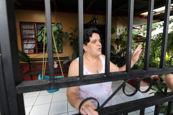 Mireya Segura tiene 20 años de vivir en el extremo norte del puente. Su esposo sembró itabos y caña india para tapar la vista que tiene la casa hacia el Virilla. Mireya ha presenciado varios suicidios y esto la afecta. Foto: Jorge Castillo