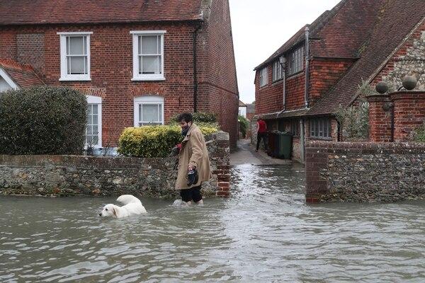 Este hombre y su perro lidiaban con la inundación en Bosham, Inglaterra, este lunes 10 de febrero del 2020, luego del azote de la tormenta Ciara.