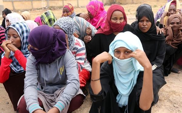 Mujeres subsaharianas detenidas en en Trípoli luego de que las autoridades libias hallaron a 760 personas listas para embarcar a Europa. | AFP