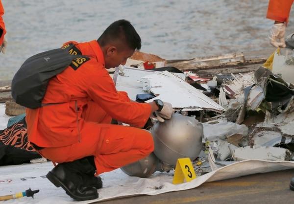 Un miembro de la Agencia Nacional de Búsqueda y Rescate de Indonesia inspecciona los desechos recuperados del área donde se sospecha que un avión de pasajeros de Lion Air se estrella, en el puerto de Tanjung Priok en Yakarta, Indonesia. Foto: AFP