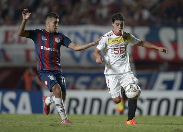 Lorenzo Faravelli de la Unión Española disputa el balón con Ángel Correa de San Lorenzo.