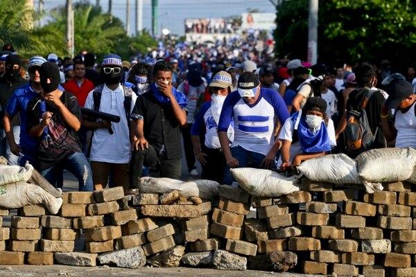Opositores al gobierno de Daniel Ortega se parapetaban detrás de una barricada en Managua, este miércoles 30 de mayo del 2018, en momentos en que había protestas.
