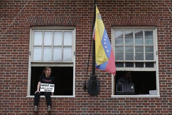 Ariel Gold de la organización activista CodePink se sienta en una ventana de la Embajada de Venezuela durante una conferencia de prensa este jueves en Washington, DC. Foto: AFP