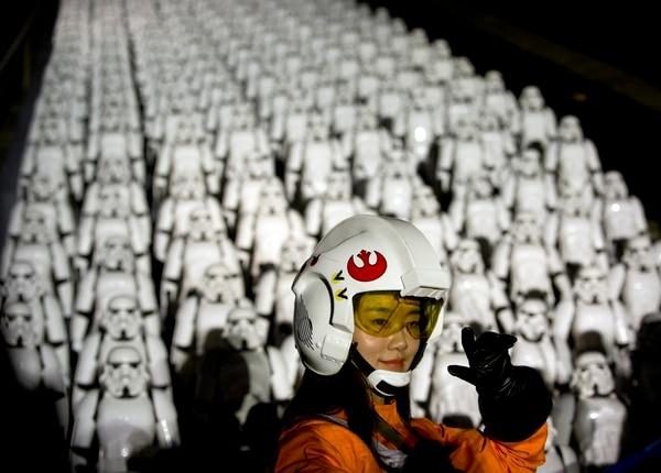 Una fan china de Star Wars posa frente a cientos de figuras de Stormtrooper durante un evento promocional de la nueva película 'Star Wars: el despertar de la fuerza'.