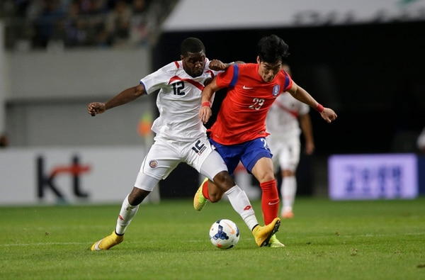 Joel Campbell cubre la pelota ante la marca del defensa coreano