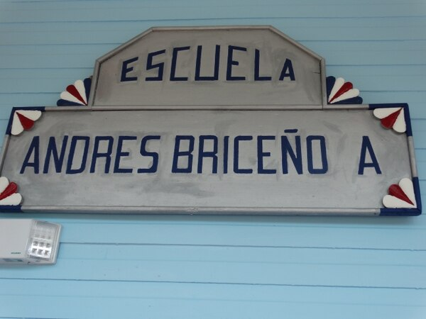 El rótulo original de la escuela, pintado en madera, se encuentra colocado en una de las paredes del centro educativo. Anteriormente se ubicaba encima de un armario polvoriento. Foto: Centro de Patrimonio Cultural.