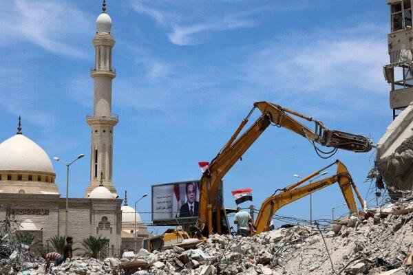 Los trabajadores egipcios y las topadoras enviadas desde Egipto ayudaron el 9 de junio del 2021 a retirar los escombros de los edificios destruidos por los ataques aéreos israelíes el mes pasado. Foto: AFP