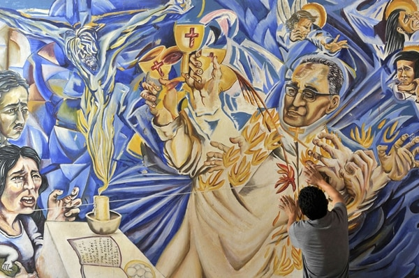 Un creyente ora y toca el mural que representa a Monseñor Óscar Arnulfo Romero en la iglesia de San Pedro Apóstol, en Ciudad Barrios, donde nació el arzobispo. El próximo 23 de de myo será beatificado. Monseñor fue asesinado el 24 de marzo de 1980 mientras oficiaba la santa misa. AFP PHOTO / Marvin RECINOS | ASDASDASD