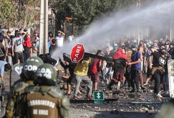 Manifestantes, algunos con mascarillas, se enfrentan con policías durante una protesta para exigir ayuda alimentaria del gobierno, en un barrio de Santiago, Chile, el lunes 18 de mayo del 2020. Foto: AP
