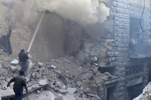 Unos civiles tratan de sofocar un incendio en el lugar donde se registró un ataque aéreo por parte del régimen sirio en el barrio de Kalase en Alepo, Siria.