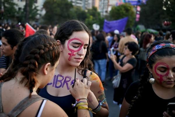 Una mujer escribe la palabra Libre sobre su amiga en una protesta del Día Internacional de la Mujer en Santiago, Chile, el jueves 8 de marzo.