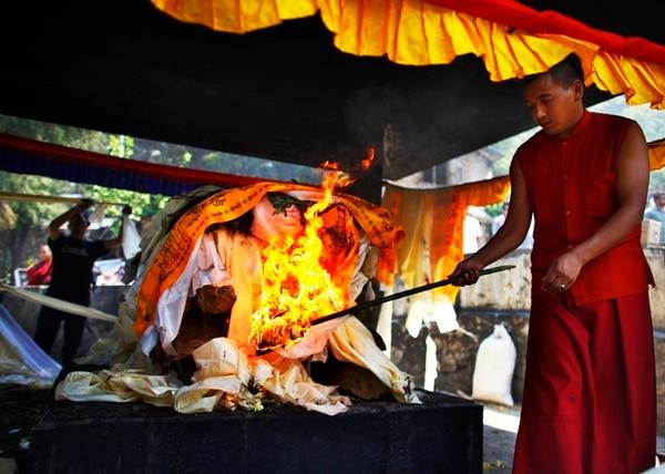 Un monje budista nepalés incinera a una de las víctimas del alud. | AP