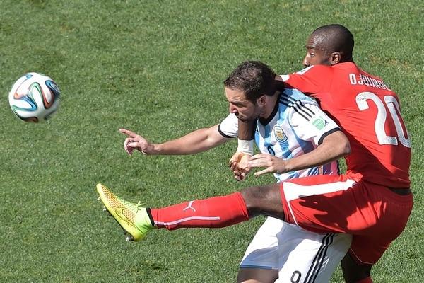 El delantero argentino Gonzalo Higuaín intenta eludir la marca del defensor suizo Johan Djourou.