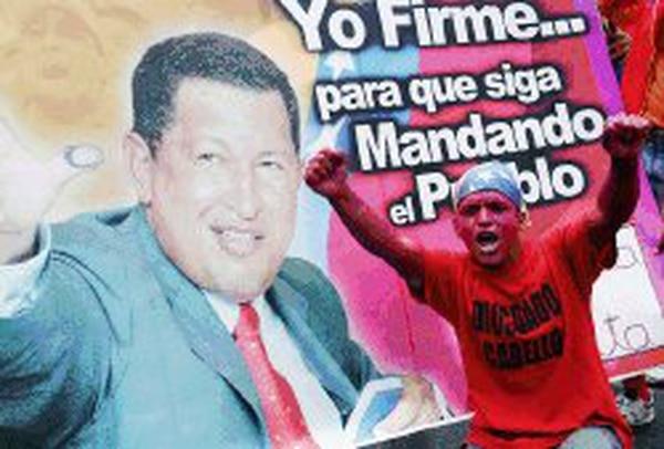 Un seguidor del presidente Hugo Chávez le gritó ayer a periodistas frente a un afiche del mandatario venezolano, durante una multitudinaria marcha en apoyo al líder en las calles de Caracas, que arrancó la campaña contra el referendo revocatorio del mandato de Chávez. Rechazo.   AP /LA NACIÓN
