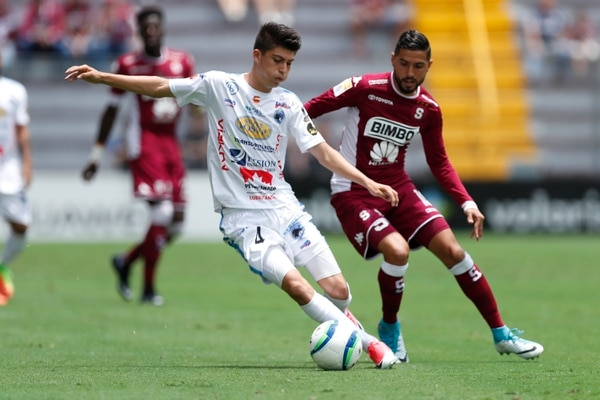Luis Hernández, el juvenil de Grecia, intenta driblar a Marvin Angulo.