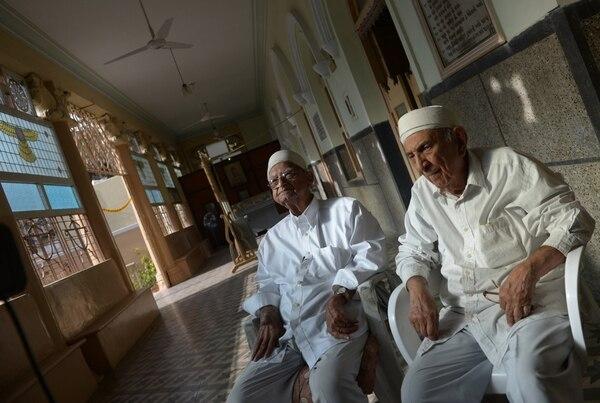 Foto de febrero del 2015 de los sacerdotes parsi pakistaníes Jehangir Noshik (izq.) y Jal Dinshaw (der.) sentados en su lugar de oración en Karachi.