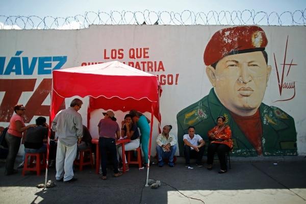 Los votantes se registran después de emitir sus votos en las elecciones presidenciales de Venezuela, en el llamado 'punto rojo' establecido fuera de un centro de votación para confirmar las tarjetas de las personas para acceder a los programas sociales administrados por el gobierno. AP