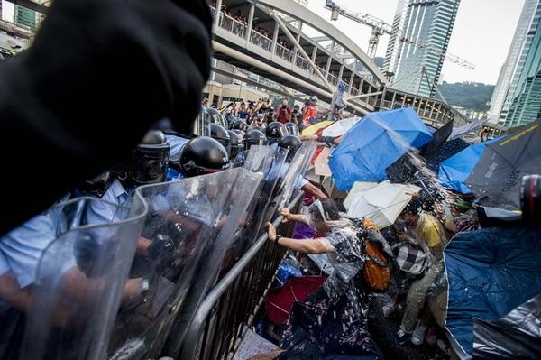 Miles de manifestantes prodemocracia se enfrentaron ayer con las fuerzas policiales antimotines en las cercanías de la sede del Gobierno de Hong Kong.   AFP