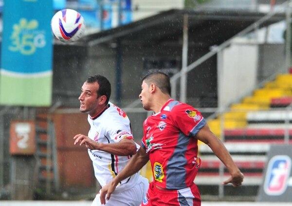 El empate dominó en Guápiles. El santista Kevin Fajardo (der.) despeja ante el belemita Cristian Carrillo. | JOSÉ RIVERA