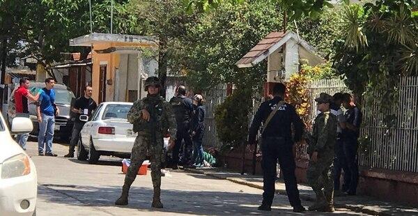 Las autoridades investigan la escena donde el periodista Ricardo Monlui fue asesinado.
