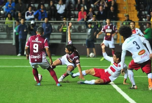 Juan Bustos disputa el balón con Johnny Acosta, lo observa Guzmán. Saucedo y Bustos fueron figuras en el Saprissa al conseguir el segundo y tercer gol. | JOSÉ RIVERA