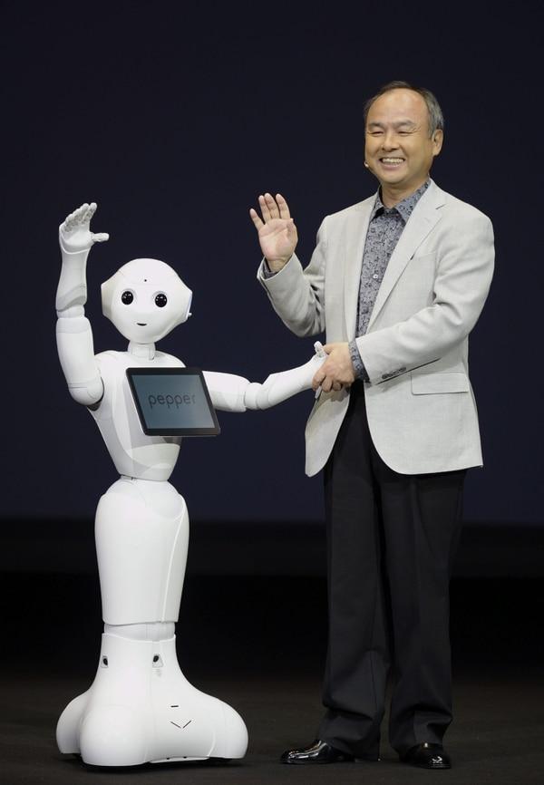 El presidente ejecutivo y presidente de SoftBank, Masayoshi Son, posa con el robot humanoide