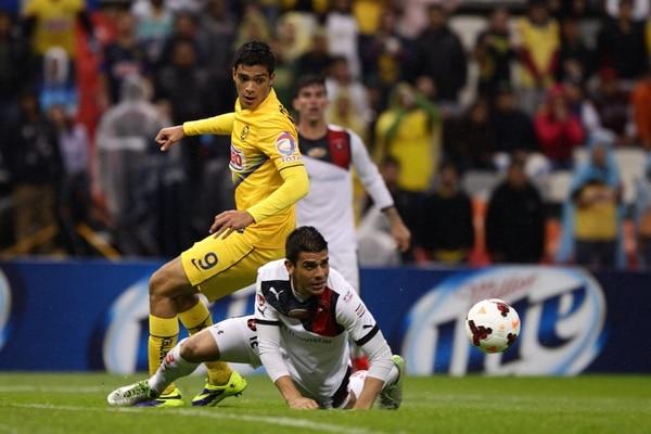 Johnny Acosta frena el avance del goleador americanista Raúl Jiménez, quien se vio deslucido ante la eficiente zaga alajuelense. | EFE