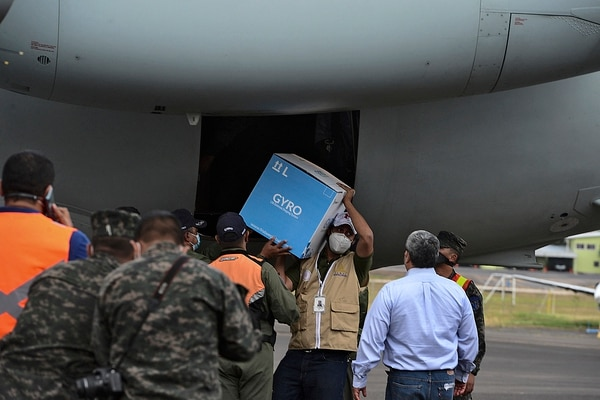 A Honduran Air Force pilot unloads a box from the presidential plane as 5,000 doses of the Moderna vaccine against COVID-19 donated by Israel arrive at the Hernan Acosta Mejia air base, in Tegucigalpa on February 25, 2021. (Photo by Orlando SIERRA / AFP)