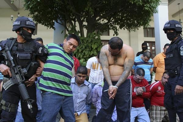 Miembros de la Policía Nacional Civil custodian a varios pandilleros detenidos durante un operativo el viernes en San Salvador. En las calles del país actúan unos 50.000 mareros, según las autoridades. | EFE