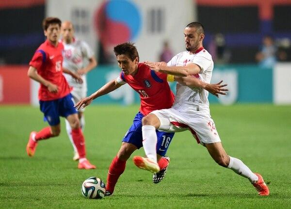 Koo Ja-Cheol (rojo) disputa el balón con el jugador de Túnez, Stephane Houcine Nater, durante el amistoso de este miércoles.