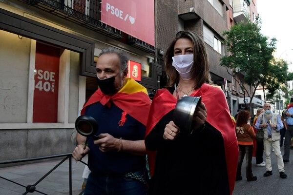 Una pareja golpea ollas durante una protesta contra el gobierno por su gestión de la crisis del coronavirus, frente a la sede del Partido Socialista, en Madrid, el 18 de mayo del 2020, a pesar del confinamiento para evitar la propagación de la enfermedad covid-19. Foto: AFP