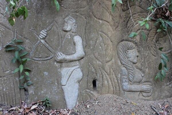Una pareja de indígenas se dan la espalda. Él posee un arco y una flecha; ella una vasija en sus manos.