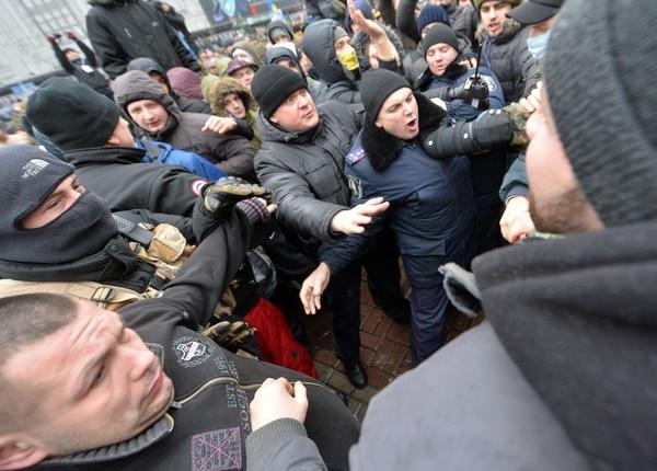 Un policía ucraniano se detiene en medio de la turba de manifestantes.