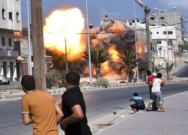 Hombres palestinos observan una explosión luego de que una bomba de un ataque aéreo israelí golpeara ayer una casa en la Ciudad de Gaza.   AFP