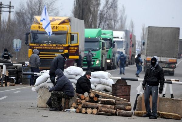 Fuerzas milicianas inspeccionan vehículos en un puesto de control en la carretera que enlaza la península de Crimea con el resto del territorio de Ucrania, cerca de la ciudad de Armyansk.