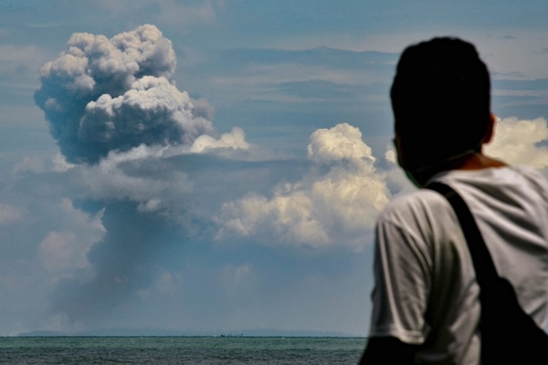 A man watches Krakatau spewing ash during an eruption, in Serang, Indonesia's Banten province on April 11, 2020. (Photo by RONALD SIAGIAN / AFP)
