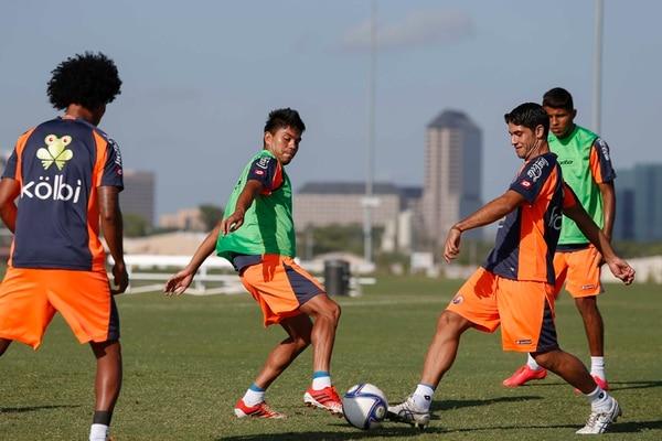 Juan Diego Madrigal (izquierda) y Pablo Salazar disputan la pelota durante el entrenamiento que realizaron ayer en una de las canchas con que cuenta el complejo deportivo Money Gram.   MAYELA LÓPEZ