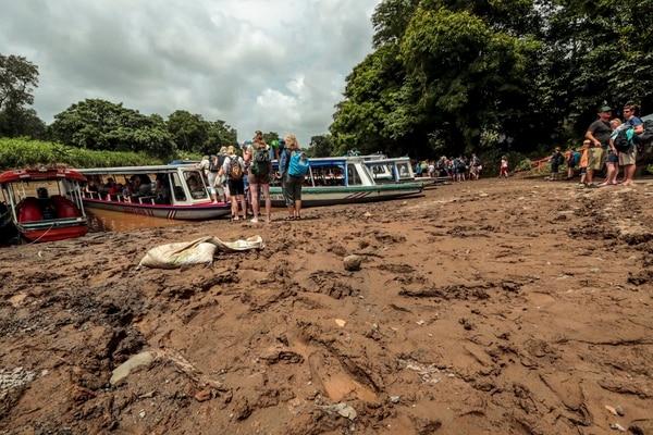 Los visitantes deben esperar en medio del barreal su turno para abordar la lancha que los llevará al Parque Nacional Tortuguero. Fotografía: Alonso Tenorio.