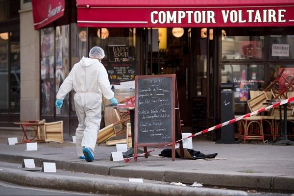 Un policía forense trabaja en la escena del Café Comptoir Voltaire.