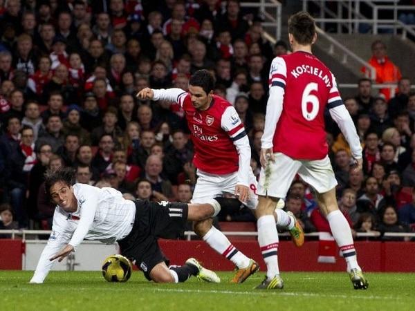 El defensor del Arsenal, Mikel Arteta (8), le comete penal al costarricense Bryan Ruiz (11). | AP