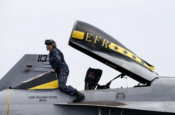 Un soldado estadounidense junto a la cabina de un avión F/A-18E Hornet en la cubierta del portaaviones estadounidense USS George Washington tras atracar en una base naval en la ciudad portuaria surcoreana de Busan.