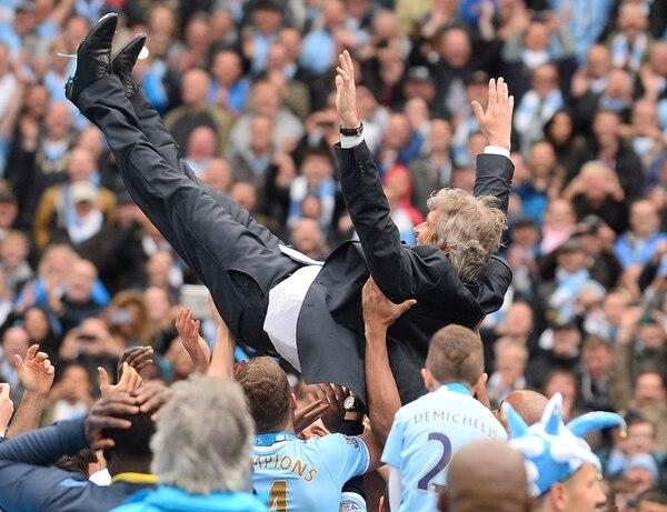 Los jugadores del Manchester City lanzan a su técnico, Manuel Pellegrini, tras ganar el título en Inglaterra. | AFP